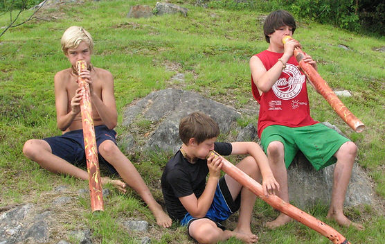 Three campers playing home made didgeridoos
