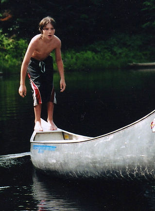 A boy balancing on a canoe in a Vermont lake