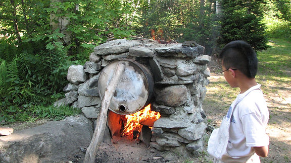 A camper watches over a homemade brick oven