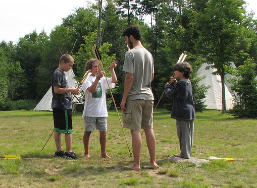Campers and staff using atlatls and darts