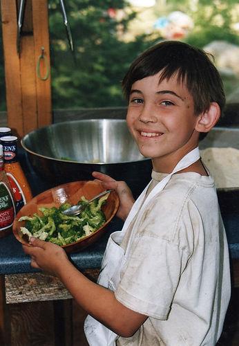 A camper shows off food he prepared