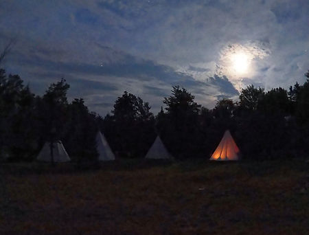 Four tipis lit by campfire during the Vermont night
