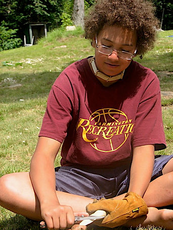 A boy whittling a carving with a knife