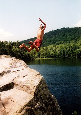 A boy jumping into Little Rock Pond in Vermont