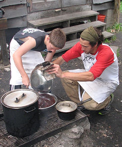 A camper and counselor cook a meal