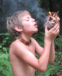 A boy starts a fire using birchbark tinder