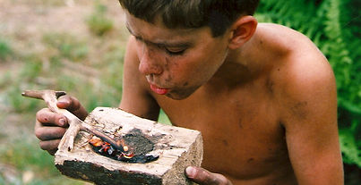 A boy uses fire to burn out a wooden bowl