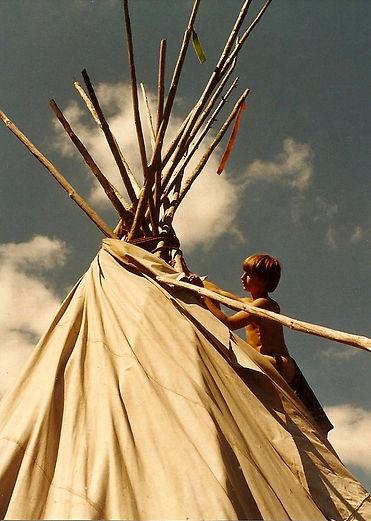 A boy climbing a Sioux tipi to install smokeflap poles