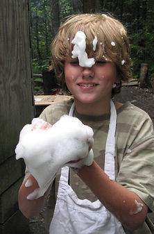 A boy in an apron plays with soap bubbles