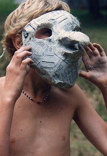 A camper wears a paper mache mask