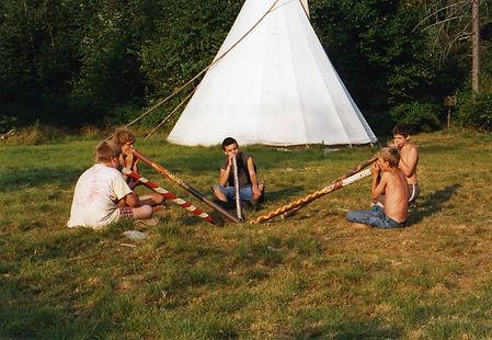 Five boys playing home made didgeridoos