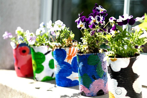 5 hand painted plant pots with flowers in sat on a window ledge with the logo for  beautifully original.com on the first plant pot.