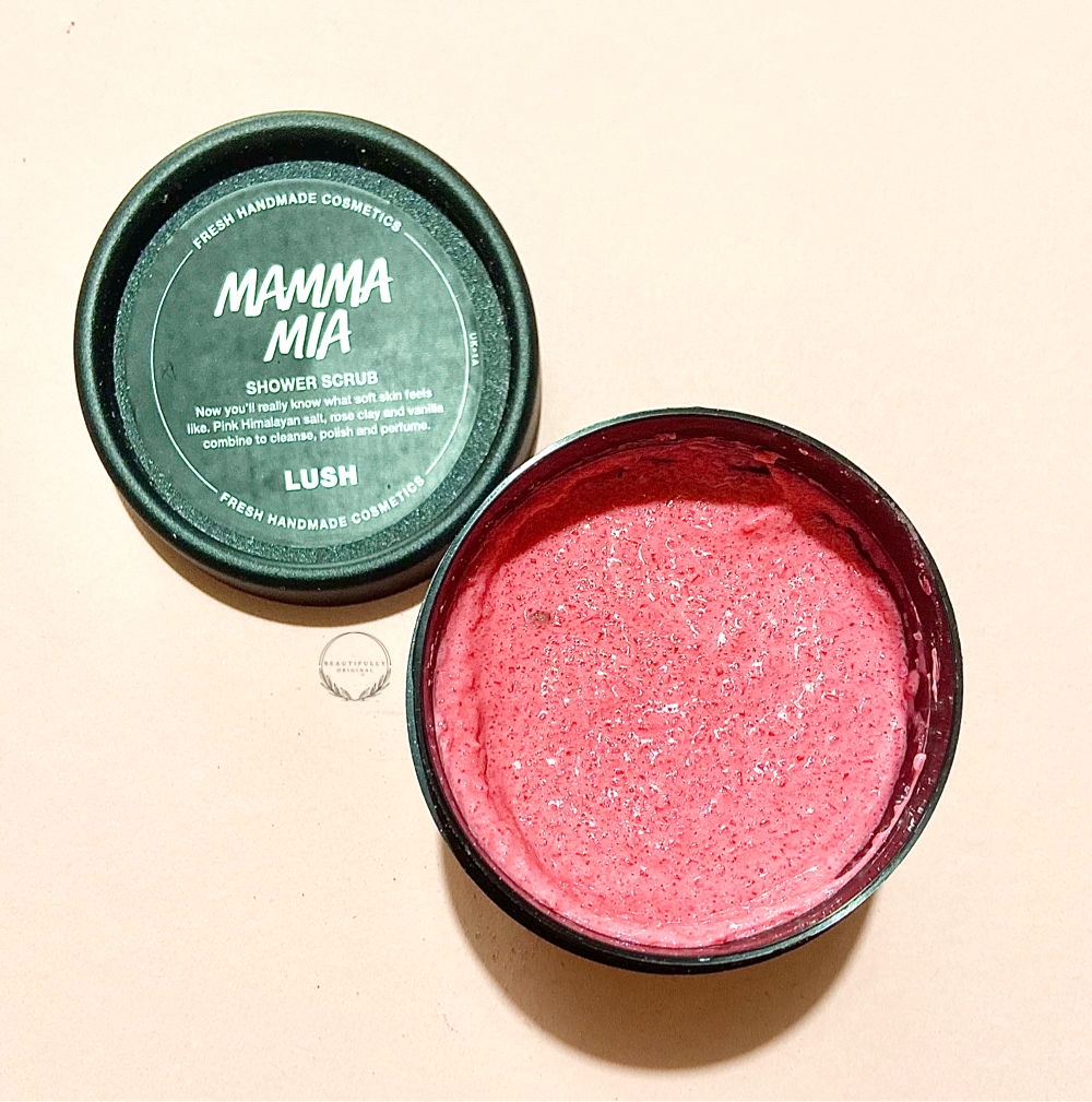 a black plastic pot of bright pink body scrub called Mamma Mia on a pink background with beautifully original logo on.