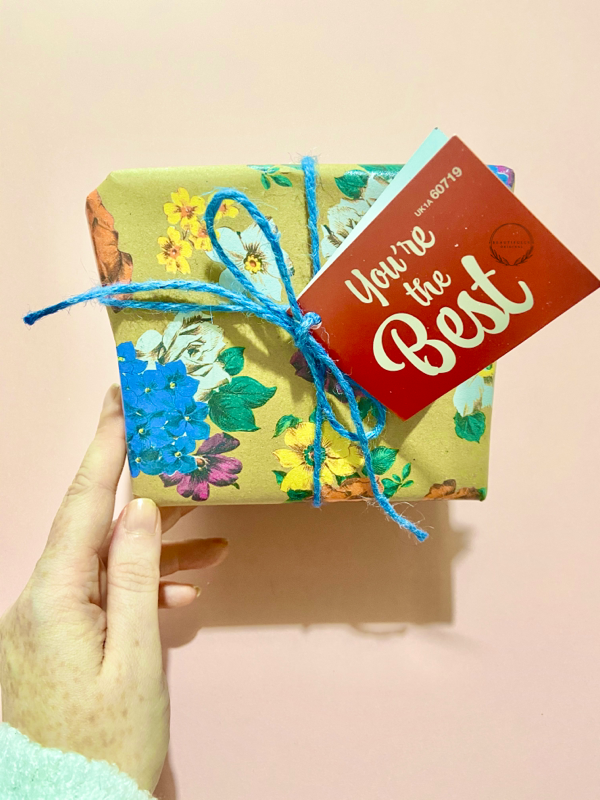 a hand holding the You're the best gift set on a pink background