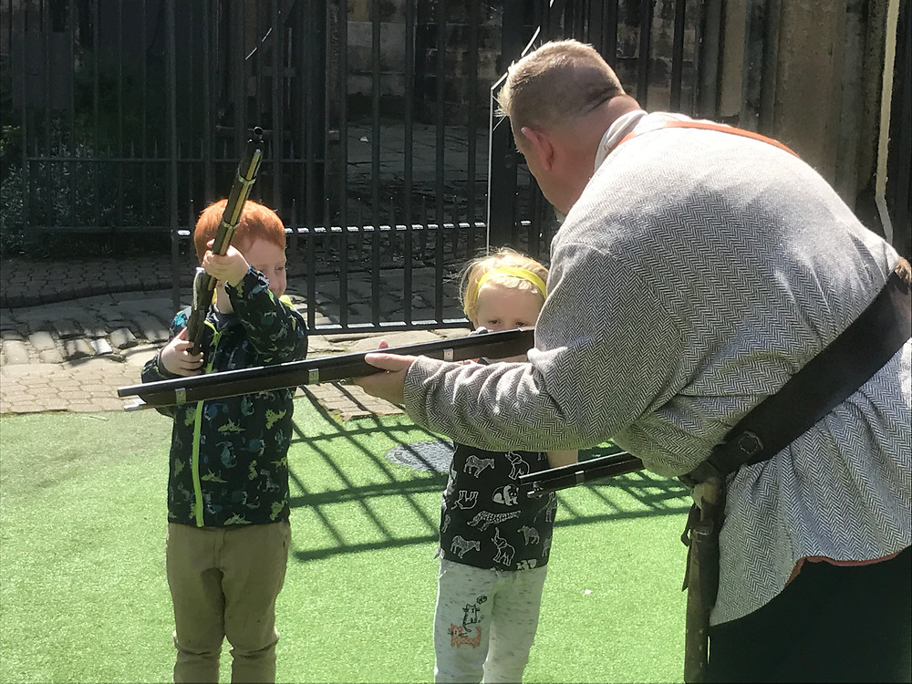 Children being taught about medieval weapons' and the way of life at Lancaster castle in the 18th century on a sunny day trip.
