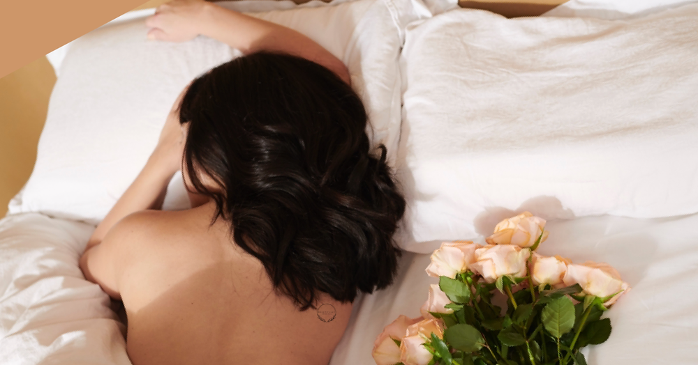 a woman happily sleeping naked in bed with a bunch of flowers next to her.