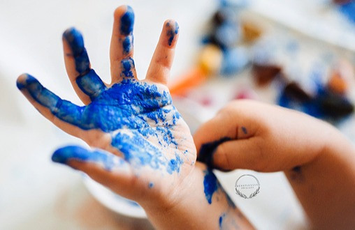a childs hand being painted blue ready to press on paper to make a picture. the background has  the logo for beautifully original