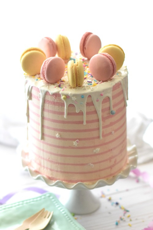 a beautiful pastel coloured Mother's Day cake with macaroons on the top