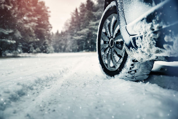 Car tires on winter road covered with sn