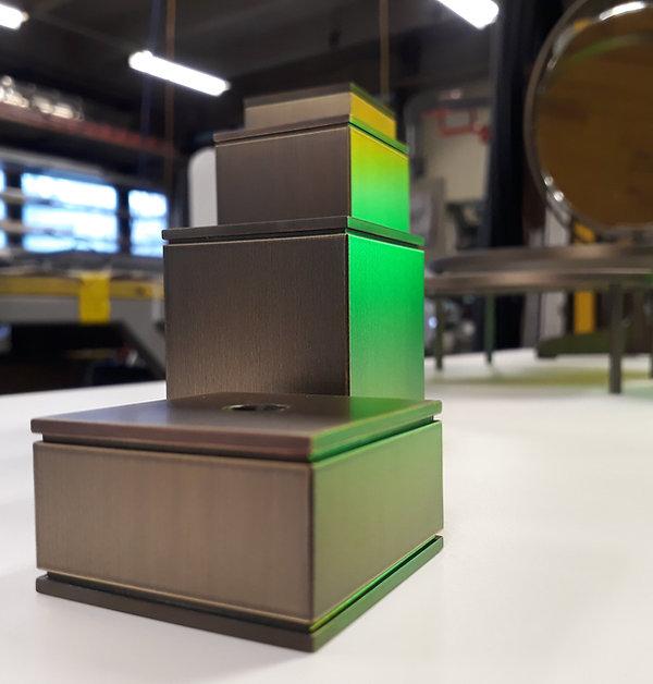 Dekoration Sockel Steller Messing Brass Luzern seitlich von grünem Licht angestrahlt