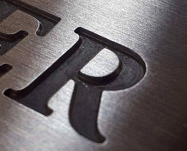Detailansicht einer miniatur Gravur Buchstabe R, ca. 0.5mm tief. in Aluminium gefräst