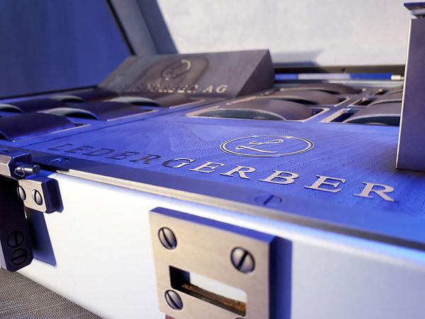 Metallkoffer Detailansicht in violetem Licht - mit Bronze Logo der LEDERGERBER AG eingelegt