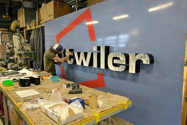 Leuchtreklame für Dettwiler AG in Reiden, Bild zeigt wie Mitarbeiter Buchstaben mit LED bestückt.