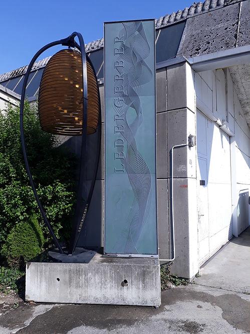 Eingang mit Pylon der LEDERGERBER AG und Grosser Lampe daneben
