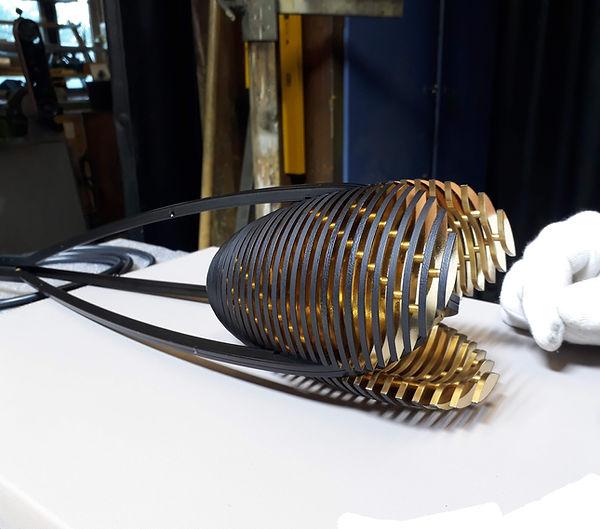 Kundenauftrag einer Designerlampe Endmontage mit weissen Handschuhen - Lampenfarbe Gold/schwarz