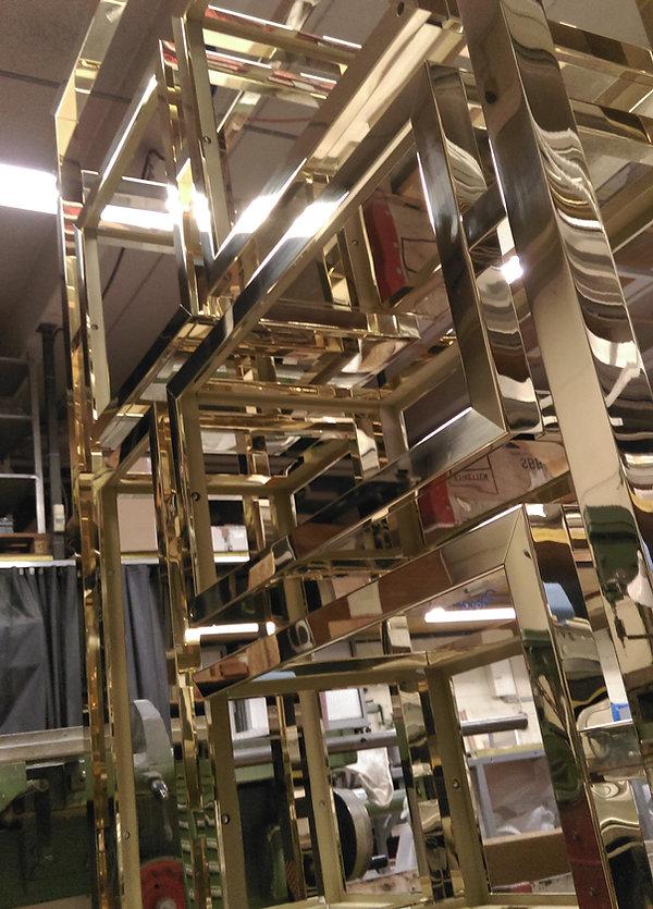Vitrine komplett in Messing poliert, glänzend und spiegelnd. Versch. Boxen in einem Rahmen hängend.