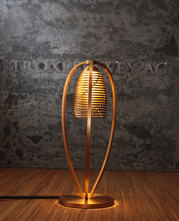 Exklusiv Leuchte in Messing vor Beton hintergrund auf Holzplatte - Honigfarbenes Ambiente