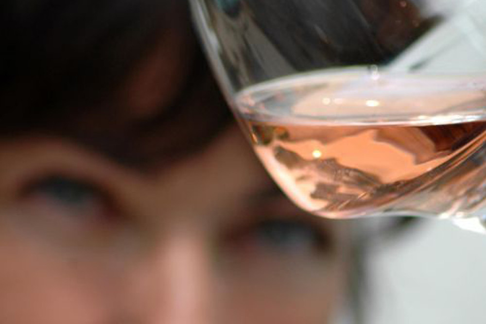 Woman looking at a glass of Provence rosé