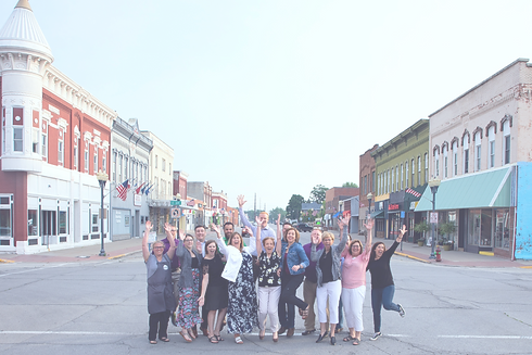 Main Street Nevada, Iowa board members celebrating in the middle of Downtown Main Street in Nevada, Iowa
