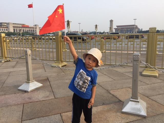 A young child holding the Chinese flag posing for his mom, but you can see from the child's face didn't want her photo taken anymore. Haha! Children are the same all over the world!