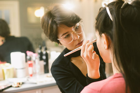 young-visagiste-applying-makeup-on-model