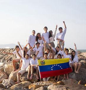 Grupo bachilleres con bandera de Venezuela en el malecón, playa y cielo