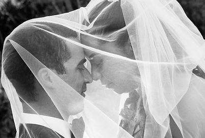 Pareja de novios recien casados debajo del velo