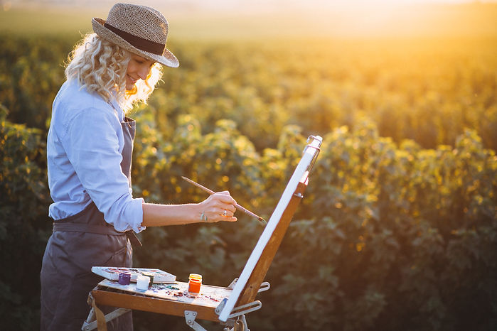 Woman artist painting with oil paints in