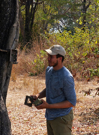 Volunteers help with camera trap surveys; Sam with one of three cameras he donated to our project