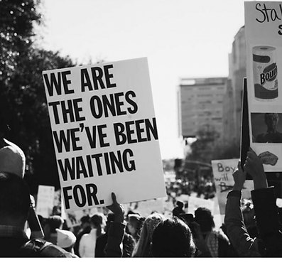 black and white image of person holding a protest poster saying we are the ones we've been waiting for.