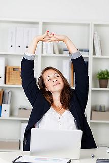 Femme qui s'étire assise a son bureau au travail. Elle est relaxée et zen. Cette image illustre un texte proposant de la sophrologie en entreprise.