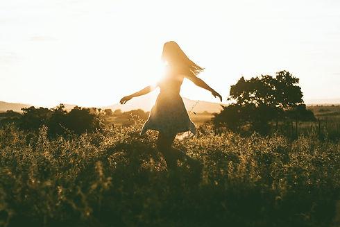 Femme qui danse et tournoie dans un champs au coucher du soleil. Joie et liberté se dégage de l'image. Son corps est libre. Liberté de mouvement.