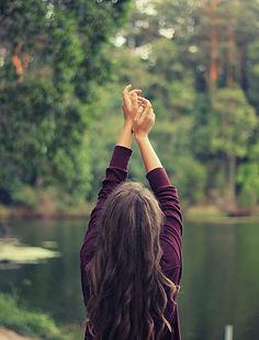 Femme face a un lac de dos. Bras en l'air. Elle semble effectuer des mouvements physiques. Ses mais se rejoingent en l'air. cette image est acollée à un texte parlant de la sophologie.