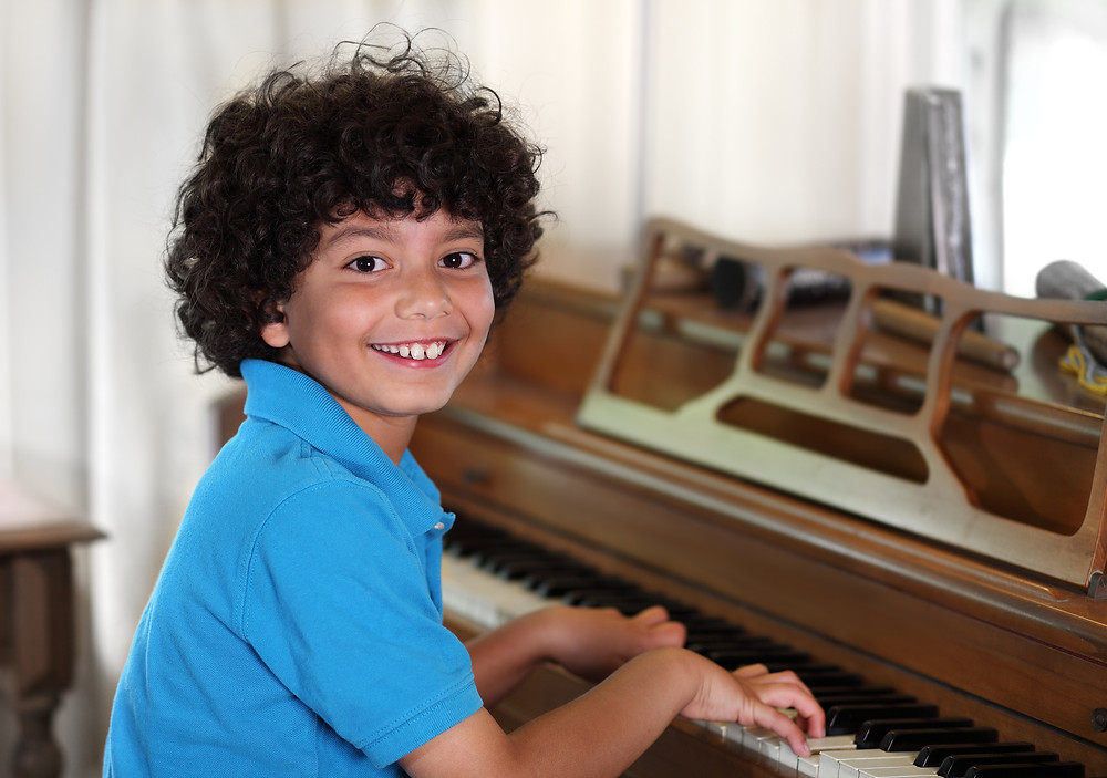 Boy smiling at the piano in Manhattan