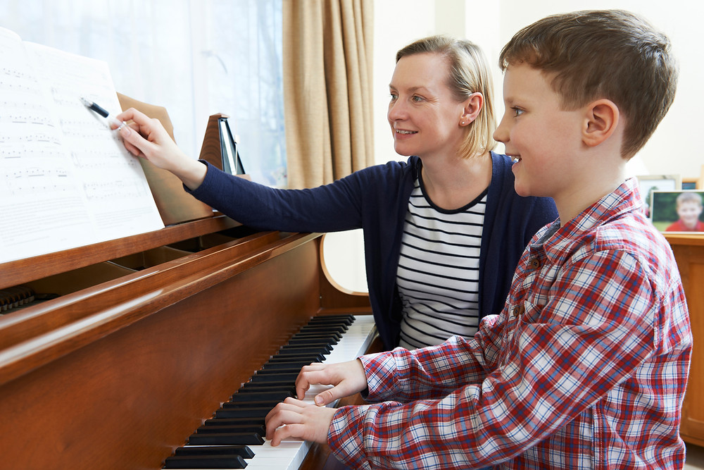 A boy takes piano lessons.