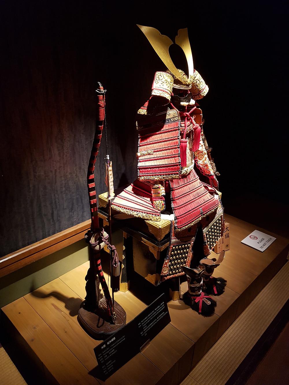 Samurairüstung und ein Bogen im Samurai Museum