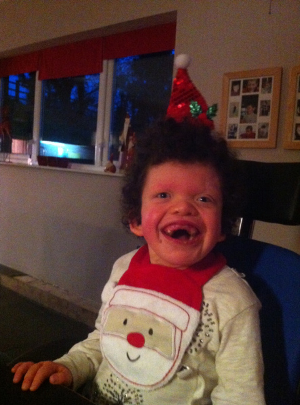 Carys in her Christmas gear beaming at the camera and enjoying her Christmas dinner.