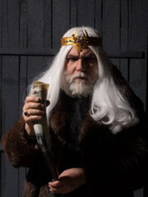 Medieval king with gold crown, snowy white hair and beard, holding drinking horn in right hand