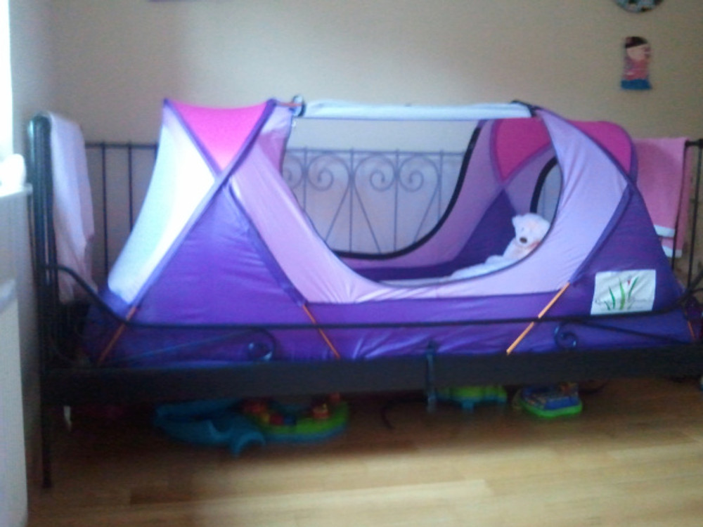 Carys's safety bed tent set up on her bed at home.