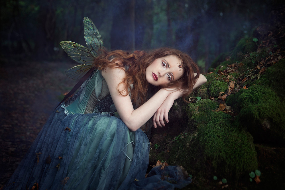 Beautiful female winged fairy being in blue dress.